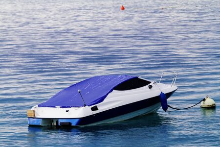 Blue and white motorboat with yellow buoy