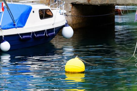 Blue and white motorboat with yellow buoy - detail photo