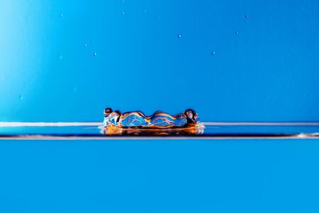 Blue water drop splashing with waves -macro photo