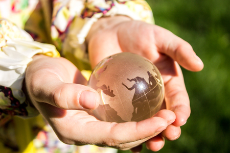 Childrens hands hold a glass globe