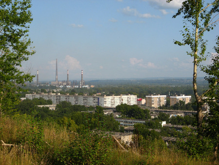 Panorama of an industrial city from the top of a hill overgrown with grass
