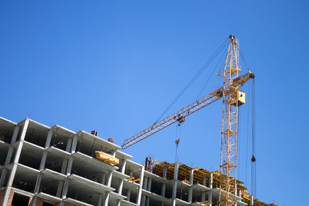 View to a house under construction and a crane against a blue sky Stock Photo