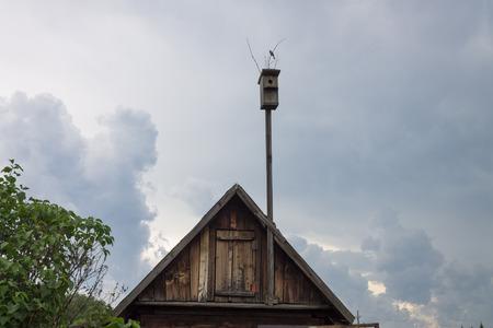 오래 된 birdhouse 오래 된 정원 집의 다락방 지붕 위에 긴 막대기에 선다. 두꺼운 구름이있는 하늘 뒤에. 에디토리얼