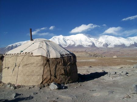 yurt and snow capped mountains