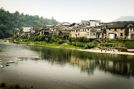 river town of wangkow, traditional buildings reflected on water photo