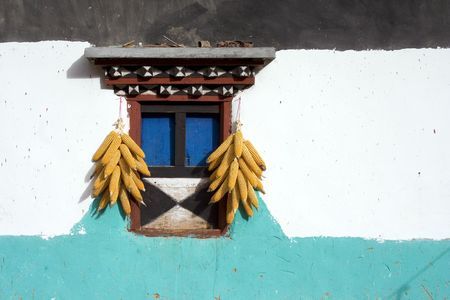 tibet, traditional house, stripes decorating facade and hanging corn
