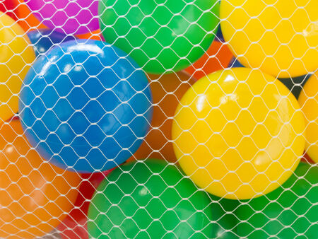 Many colour plastic balls in net from childrens small town photo