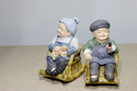 grandparent: lovely grandparent doll siting rocking bamboo chair on wood background. -still life.