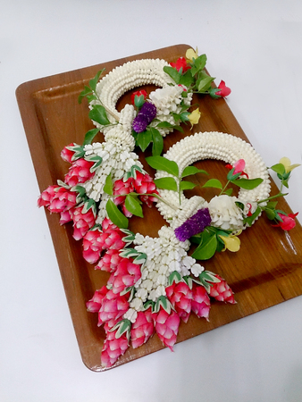 malai: Jasmine garland Thai on wood tray have unique ways of arranging flowers and using them in decorations, which are different from other places. Thai garlands called Phuang Malai