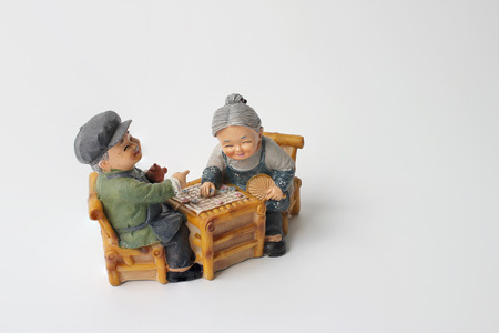 lovely grandparent doll siting rocking bamboo chair with playing checkerboard.
