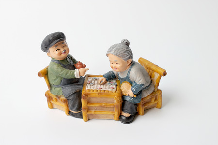 grandparent: lovely grandparent doll siting rocking bamboo chair with playing checkerboard. Stock Photo