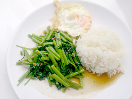Food Thai in Asian, Stir Fried Water Spinach with rice on white plate,  Vegetarian Food, healthy food