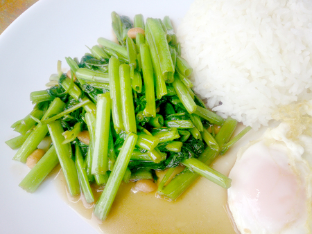 Food Thai in Asian, green morning glory vegetable fried oil with garlic food on wood table at outdoor sunlighte, Vegetarian Food, healthy food