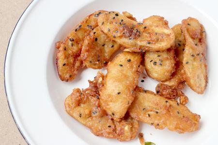 platanos fritos: Los plátanos fritos roció de sésamo deliciosa comida tradicional en el plato blanco sobre fondo de madera. - Thai Snack