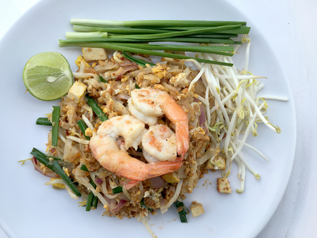 Pad Thai, stir-fried rice noodles with shrimp in white dish on white background. The one of Thailands national main dish. the popular food in Thailand. Thai Fried Noodles Stock Photo