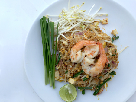 red onions: Pad Thai, stir-fried rice noodles with shrimp in white dish on white background. The one of Thailands national main dish. the popular food in Thailand. Thai Fried Noodles Stock Photo