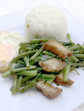 Stir Fried Water Spinach with chili and soy sauce and crispy pork on white dish isolated on white background, Thai Food.