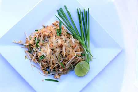 red onions: Pad Thai, stir-fried rice noodles with shrimp in white dish isolated on white background. The one of Thailands national main dish. the popular food. Thai Fried Noodles