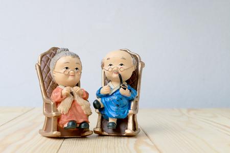 mooie grootouder pop siting oude sofa klassieke stoel samen op houten tafel met achtergrond.
