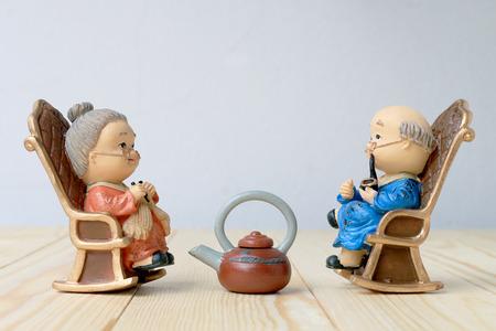 Preciosa muñeca abuelo emplazamiento viejo sofá silla clásica juntos en la mesa de madera con el fondo. Foto de archivo - 70011389