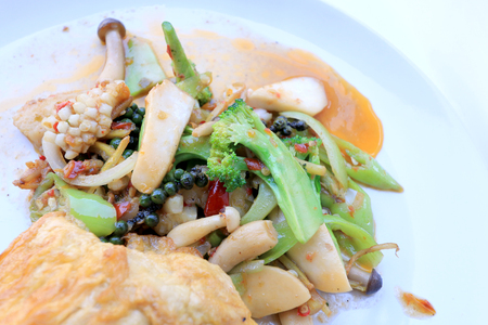 pincers: Stir fried Spicy Seafood with black pepper and thai style omelette with rice on white dish,  Thai spicy herb food  Image select focus