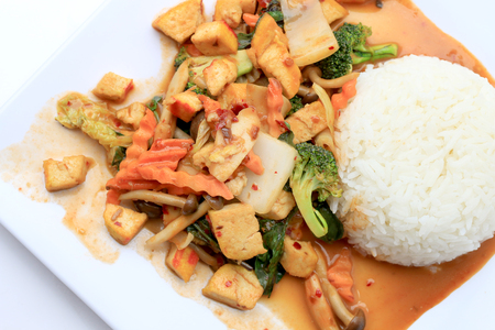 Stir Fried Tofu with Gravy Sauce and mixed vegetables in white plate on white background. Vegetarian Food, healthy food. Stock Photo