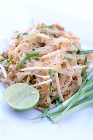 Pad Thai, stir-fried rice noodles with shrimp in white dish isolated on white background. The one of Thailands national main dish. the popular food. Thai Fried Noodles