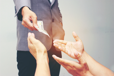 Businessman hand holding US dollar, USD. bills, offers dollar bank note money and giving money Paid for Something by Cash in Business Concept.