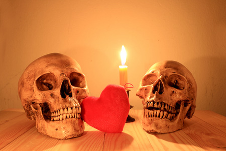 human skull and red hearts with light candle on wooden table in night time, still light photography.