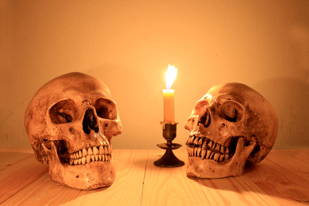 human skull with light candle in night time, still light photography.