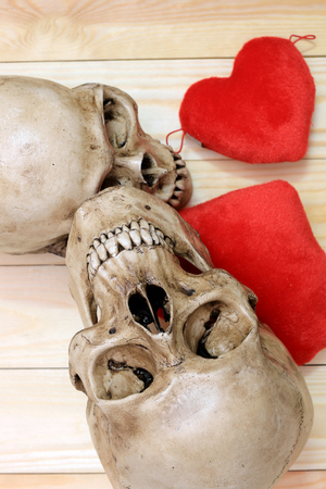 human skull with red heart on wooden background, top view. Still life Image and select focus