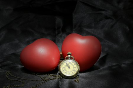 soulmate: vintage clock and red heart on black background ,Love and time concept in still life photography.