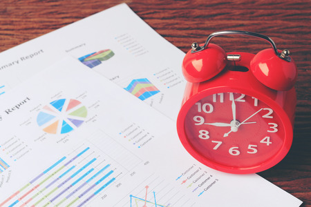 tabel: red clock on chart on wooden background. Business background , finance, tax, accounting. Concept time to wake up. Stock Photo