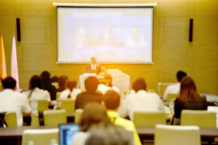 Blurred image of education people, business people and students sitting in large hal with screen and projector for showing information Stock fotó