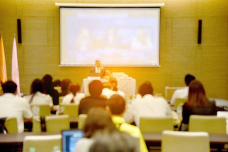 Wazig beeld van het onderwijs mensen, zakenmensen en studenten zitten in de grote hal met een scherm en de projector voor het tonen van informatie Stockfoto