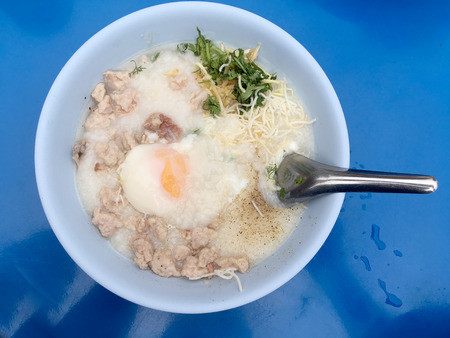 Traditional thai porridge rice gruel in white bowl, congee. In the street night market.