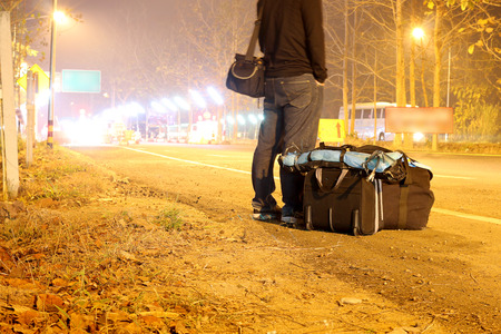 Vintage suitcases, photo camera on road with light motion with slow speed shutter,Street lights in speeding car in night time. concept of travel.