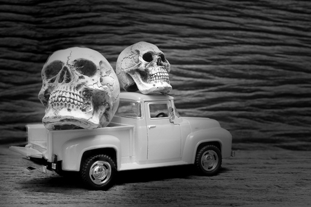 black and white shot of Still life painting photography with human skull on vintage image of pickup truck toy on wooden background.