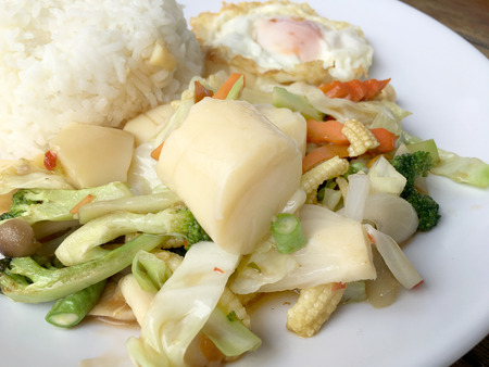Stir-fried mixed vegetables with tofu and fried egg with rice in white dish on wooden background.  Vegetarian Food, healthy food.