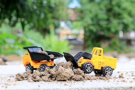 Truck toy car with sand and soil on the concrete floor with blur boken green environment  construction equipment at work ,construction concept, selective focus.