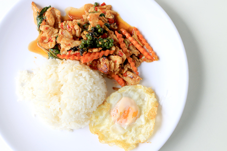 stir fried chicken with roasted chili paste and fresh Piper nigrum on jasmine rice in white plate on white background. Thai style food. Stock Photo