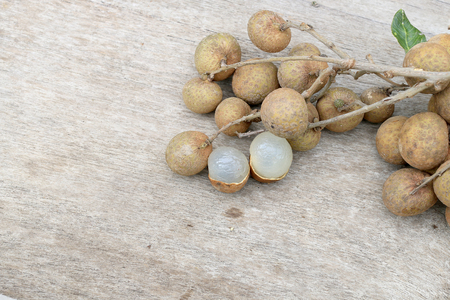 black family: Longan Fresh. A bunch of Longan and Peel on a wooden background with green natural background in the garden from northen Thailand.  sweet and fragrant,The brown fruit looks like a sphere.