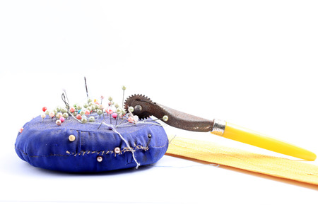 Blue handmade felt pin cushion with multicolored sewing pins stuck in isolated on white background.
