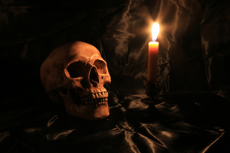 Still Life of skull  with fetters and candle on black fabric with texture with candle light in dim light night. image tone from candle light in night time.