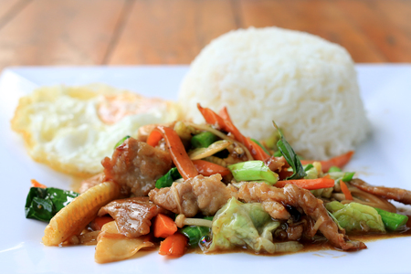 Delicious Thai dish chicken with stir fried vegetables in white dish with rice and fried egg on wooden table. Thai food. Stock Photo