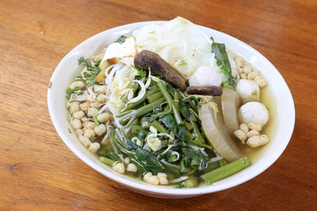 vietnamse: vietnamse noodle soup, served with fresh herbs at the buddhist eatery, radish, morning glory, shiitake and tofu in white bowl on Wood table in Vegetarian Festival.