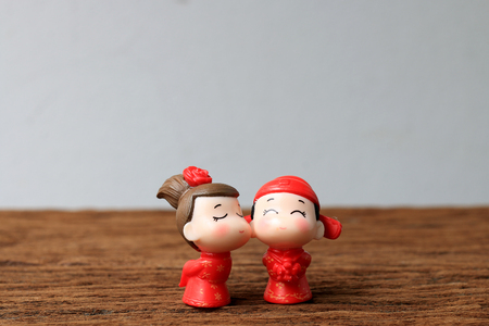 wedding couple of Lover Chinese New Year doll in chinese uniform style stand on wooden table with background wall. Stock Photo