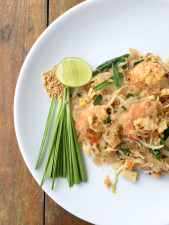 Pad Thai, stir-fried rice noodles with shrimp in white plate on wood table. The one of Thailands national main dish. the popular food in Thailand. Thai Fried Noodles