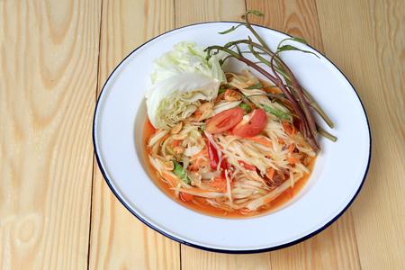 Sałatka Papaja z marchewką, soczewica, pomidor, suszone krewetki, chili, w białej płytce na drewnianym tle. Tajski styl żywności.