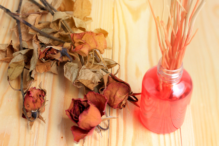 Hand made pf Fragrance Diffuser Set: bottle with aroma sticks and dry red rose (reed diffusers), a spray bottle with perfume on pine wood table with wall background.